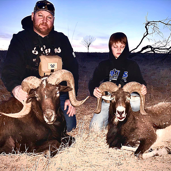 Father and son posing with their trophies after ram hunt.